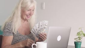 Close up shot of retired old woman grandmother show a bundle of money dollars while seating at the laptop at home