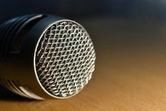 Close up shot of retro microphone on wooden desk. With blurred warm dark background stock images