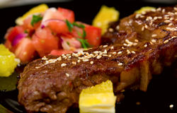 Close-up shot of ribeye steak. With tomatos and pineapple pieces on black glass plate. Focus is on sesame buns Royalty Free Stock Photos