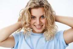 Close-up shot of romantic passionate and flirty good-looking european young woman with short curly blond haircut and. Blue eyes holding hands behind head and royalty free stock photos