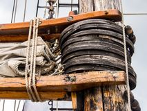 Close Up Detail of Sail Rigging, Old Ship Mast. A close up shot of the rope, wood, and sail of the rigging on an old ships mast Stock Photography