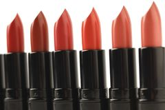 Close-up shot of row of red lipsticks of various shades. Isolated on white Stock Photography