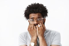 Close-up shot of scared and insecure young african american man with afro hairstyle in watch and glasses biting royalty free stock photography
