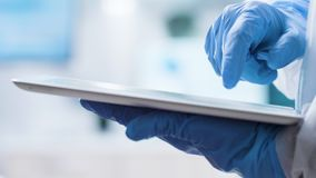Close up shot of scientist in gloves typing on a tablet PC screen