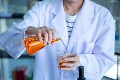 Close up scientist hand pouring orange liquid royalty free stock images