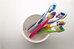 Close up shot of set of multicolored toothbrushes in glass on cl Stock Image