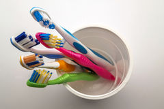 Close up shot of set of multicolored toothbrushes in glass on cl Stock Images
