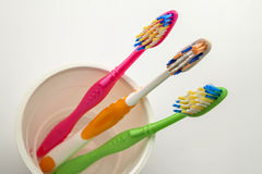 Close up shot of set of multicolored toothbrushes in glass on cl Royalty Free Stock Images