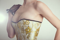 Close-up shot of sexy young woman in corset with golden embroide Stock Photography