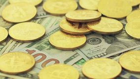 Falling bitcoins on heap of bills stock footage