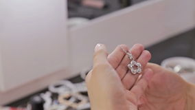 Close up shot of shiny pendant in woman`s hands stock footage