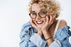 Close-up shot of silly romantic and lovely european female student in glasses and denim jacket wearing lipctick leaning stock photo