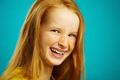 Close-up shot, sincere laughter of cute baby girl with red hair and freckles on blue isolated. Concept of happiness. Close-up shot, sincere laughter of cute baby Stock Photos
