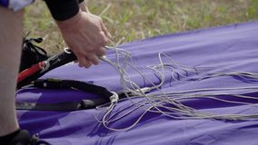 Close up shot of a skydiving instructor packing, preparing equipment for the jumping, parachute straps.