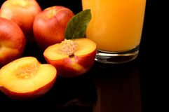 Close-up shot sliced orange nectarines with juice and leaf Royalty Free Stock Photo