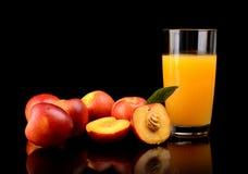Close-up shot sliced orange nectarines with juice and leaf. Studio shot of sliced orange nectarines with leaf and nectarine juice isolated on a black background stock photo