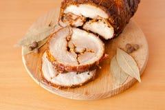 Close up shot of sliced pork meatloaf. Sliced pork meatloaf on wooden cutting board on light wooden background with bay leaves and black pepper Royalty Free Stock Photo