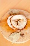 Close up shot of sliced pork meatloaf. Sliced pork meatloaf on wooden cutting board on light wooden background with bay leaves and black pepper Stock Image