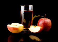 Close-up shot sliced red apple with juice. Studio shot of sliced red apple with leaf and apple juice isolated on a black background Royalty Free Stock Image