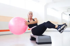 Close-up shot of slim fitness instructor exercises with fitball. Abdominal, sports equipment Royalty Free Stock Photos