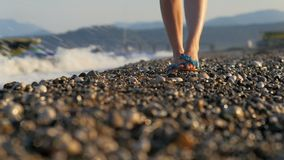 Close-up shot of slim woman`s legs moving to camera, pebble coast and panorama of mountains. At sunset, powerful sea waves are washing shore stock footage