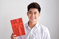 Close-up shot of smiling casual man holding present box in hands Royalty Free Stock Image