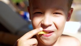 Boy enjoying fries snack at the beach. Close-up shot of a smiling kid having fast food snack at the beach, he eating French fries stock video