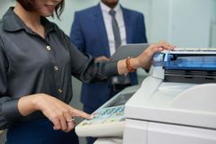 Office Assistant Using MF Printer. Close-up shot of smiling office assistant using multi-function printer in order to make copy of document, male colleague with royalty free stock image