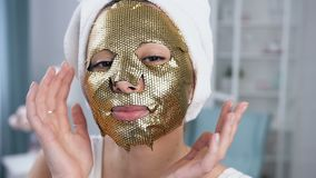 Close up shot of smiling woman fixing rejuvenating cosmetic golden tissue mask on face. Close up shot of smiling woman with towel on head fixing rejuvenating stock footage