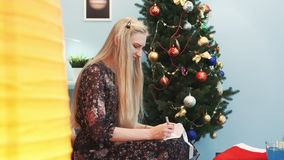 Close up shot of smiling young laddy writing a letter to Santa Claus. She is sitting on sofa near the Christmas tree and big standing lamp. Profile view stock footage