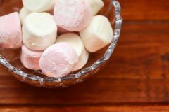Pink And White Marshmallows In Glass Bowl On Wooden Table. A close up shot of some fluffy pink and white marshmallows in a glass bowl on wooden table stock photography