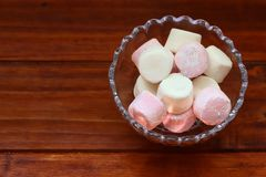 Pink And White Marshmallows In Glass Bowl On Wooden Table. A close up shot of some fluffy pink and white marshmallows in a glass bowl on wooden table Royalty Free Stock Photography