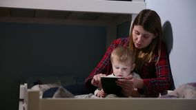 Close-up shot of son and mother in bed playing game on touch pad. Bedtime entertainment. stock video footage