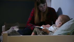 Close-up shot of son and mother in bed playing game on touch pad. Bedtime entertainment. stock video