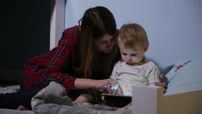 Close-up shot of son and mother in bed playing game on touch pad. Bedtime entertainment. stock footage