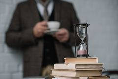 Close-up shot of stack of books and hourglass with man. Drinking coffee blurred on background Stock Image
