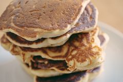 Close-up shot of stack of homemade pancakes, fresh and hot prepare before pouring syrup in white dish on wooden table, selective royalty free stock photography