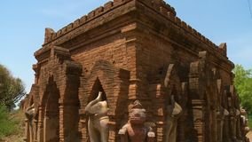 Statues built around a temple. A close up shot of statues of elephants and other animals surrounding an ancient building stock footage