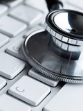 Close up shot of stethoscope on laptop keyboard Stock Photography