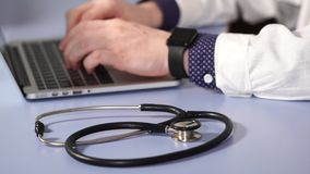 Close up shot of a stethoscope that lies next to the doctor`s hands stock video footage