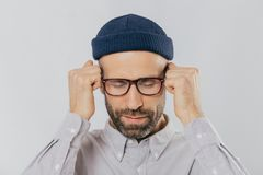 Close up shot of stressful unshaven man keeps hand near temples, has terrible headache, suffers from pain, wears headgear, stock image