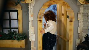 Close-up shot at the studio. The little girl enters the house and closes the door after stock footage