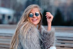 Happy blond pretty girl in coat and glasses close up portrait Royalty Free Stock Photography