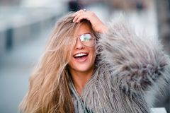 Happy blond pretty girl in coat and glasses close up portrait stock photography