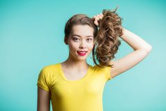 Close up shot of stylish young woman smiling against blue background. Beautiful female model collected hair hands and looks with a stock image