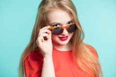 Close up shot of stylish young woman in sunglasses smiling against blue background. Beautiful female model with copy space. stock photos