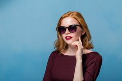 Close up shot of stylish young woman in sunglasses smiling against blue background. Beautiful female model with copy space Royalty Free Stock Image