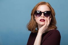 Close up shot of stylish young woman in sunglasses smiling against blue background. royalty free stock image