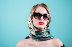 Close up shot of stylish young woman in sunglasses and you colored shawl, headscarf, scarf against blue background. Beautiful fema royalty free stock photography