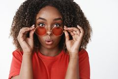 Close-up shot of surprised and amused attractive feminine african american girl with curly hair taking off sunglasses. And fold lips from amazement and interest stock photo